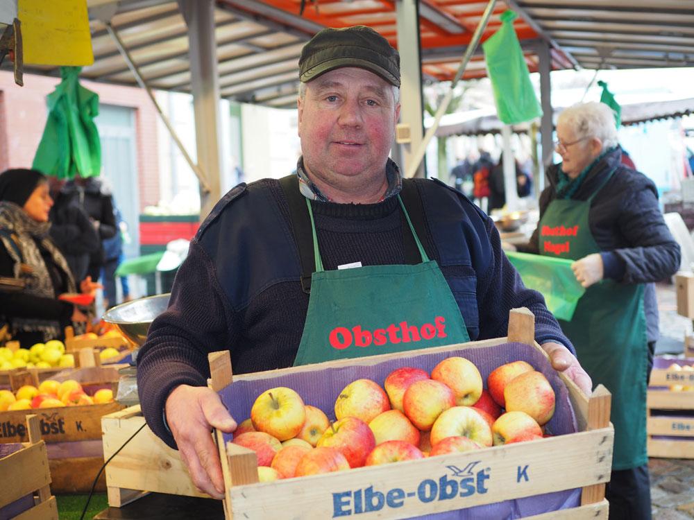 """Marktmeister """"Apfel-Willi"""" Nagel an seinem Stand auf dem Wochenmarkt. Foto: Fischer"""